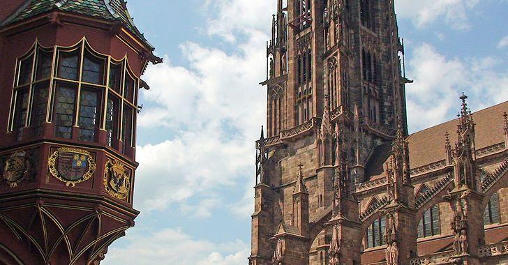 Freiburger Münster mit Turm und ein Erker des Kaufhauses am Marktplatz